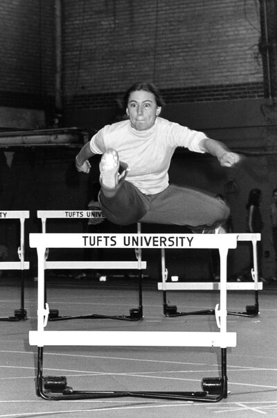 Woman leaping over a track and field hurdle, with one leg parallel to the floor in front of her and another parallel to the floor behind her